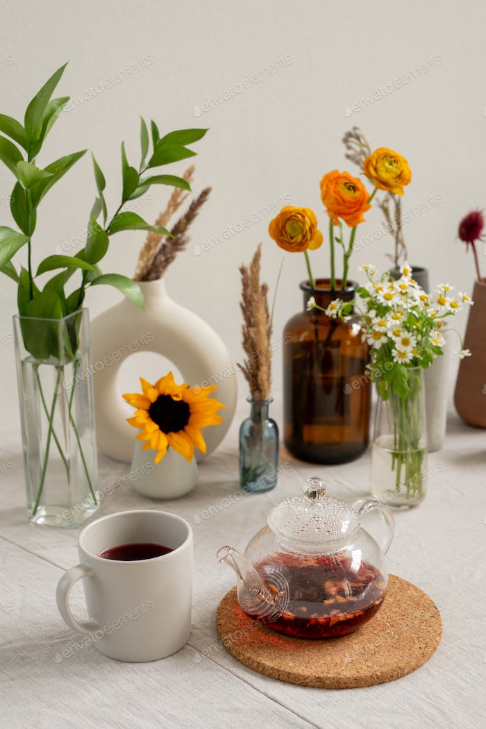 Kitchen table with porcelain mug, teapot with black tea and flowers in vases
