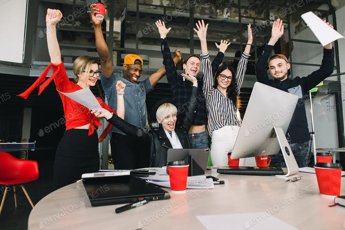 Great news. Happy smiling businesspeople in casual clothes triumphing with arms up while looking at
