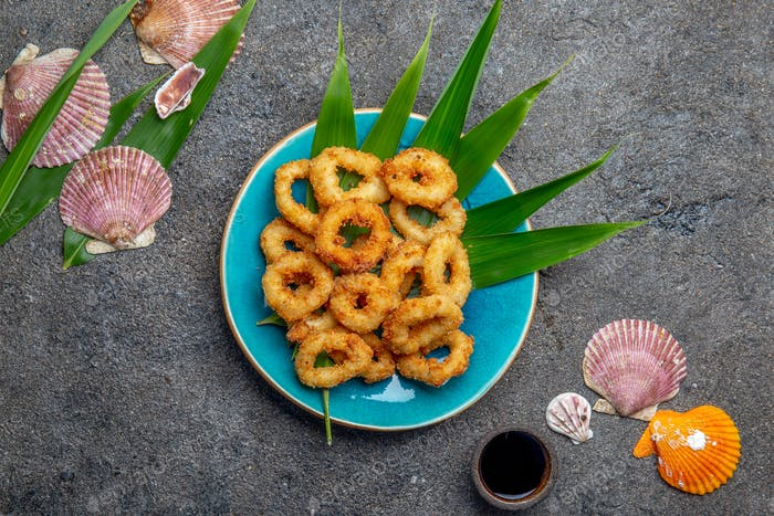 Fried squid rings. Top view, gray background.