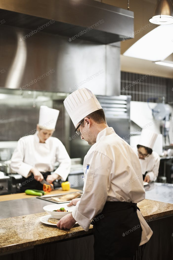 Eine Crew von Chefkoch arbeitet in einer kommerziell Küche,
