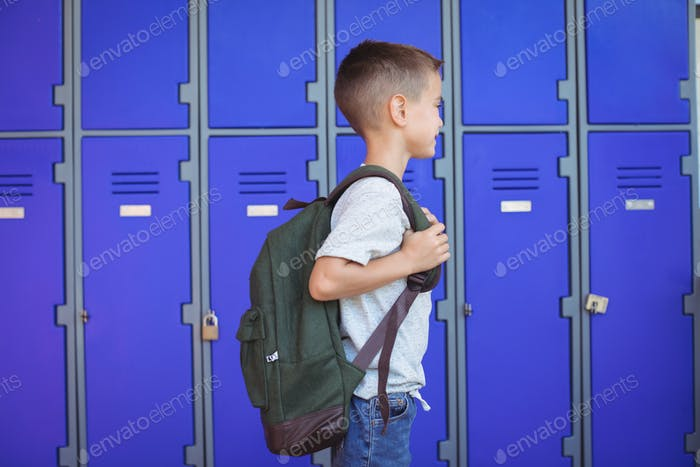 Side view of boy carrying backpack against lockers