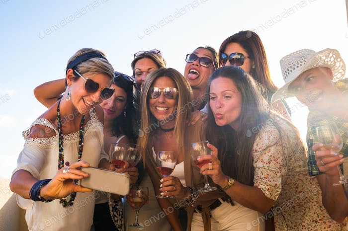 Group of young happy women enjoying aperitif on the terrace celebrating a party together