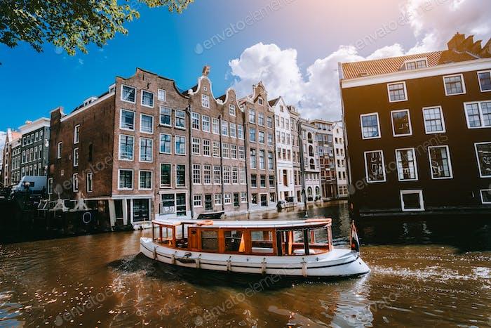 Stadt Amsterdam in Holland malerische Landschaft, weiße Boote auf einem Kanal zwischen historischen Häusern