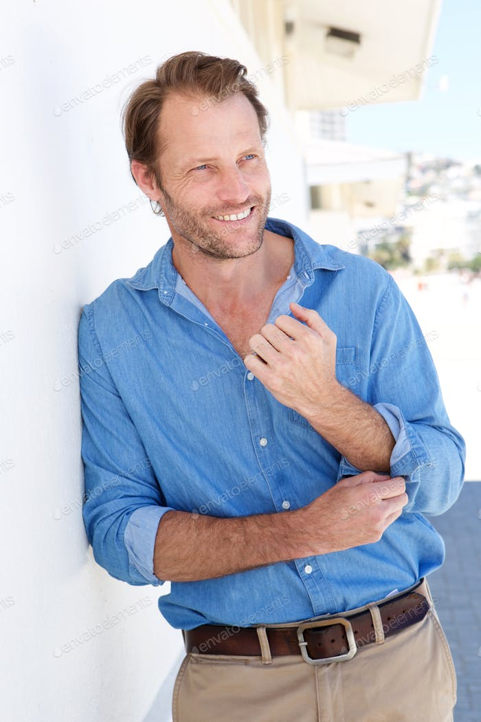 handsome man in blue shirt leaning against wall outside