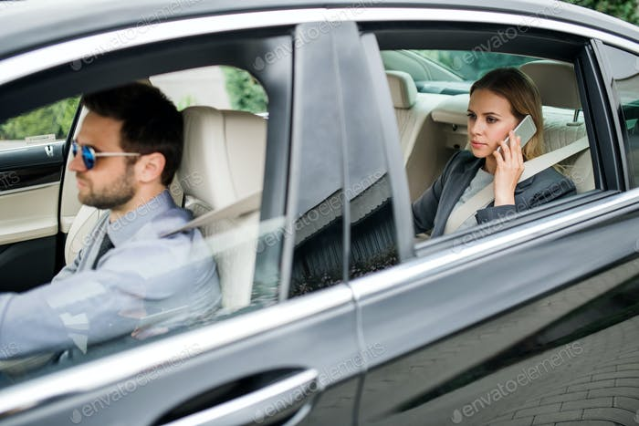 Businesswoman sitting on back seat in taxi car, talking on the phone.