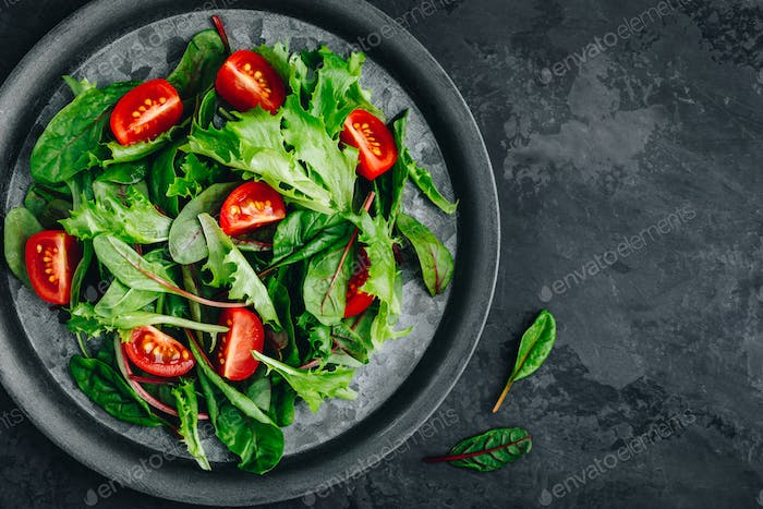 Fresh green mixed lettuce salad bowl with tomato on dark background.
