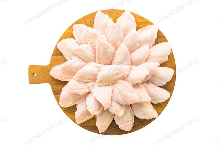 Rohes Hühnerfleisch und Flügel auf Holzschneidebrett oder Teller