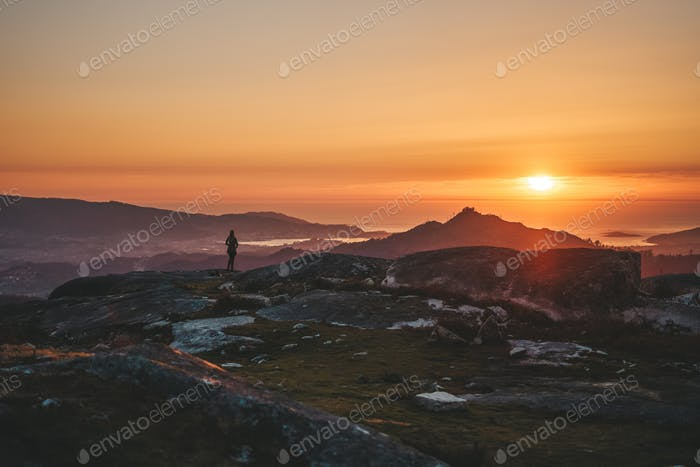 Young woman contemplating the sunset from Mount Galiñeiro in Vigo, Galicia, Spain