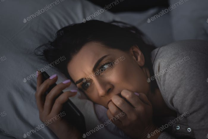 scared woman with insomnia using smartphone in bedroom