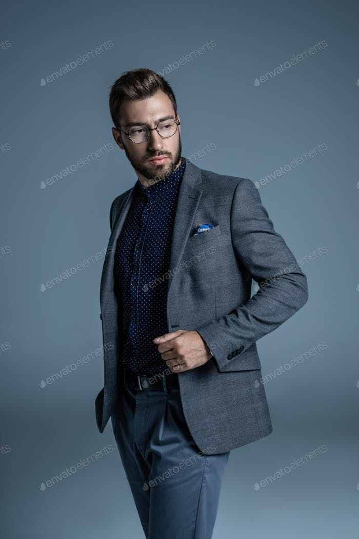 Young handsome businessman in formal suit and glasses