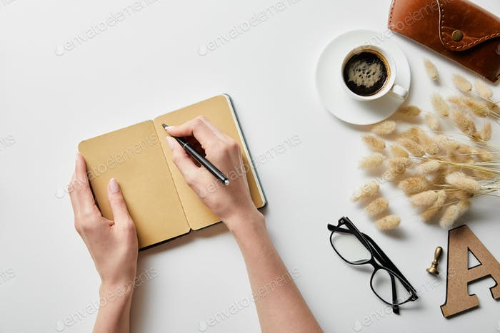 cropped view of woman writing in notepad near coffee, glasses and case on white surface