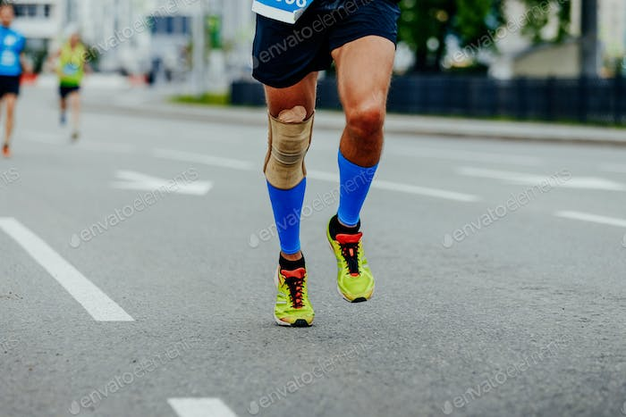 legs runner men in compression calf sleeves and kneepad running in city