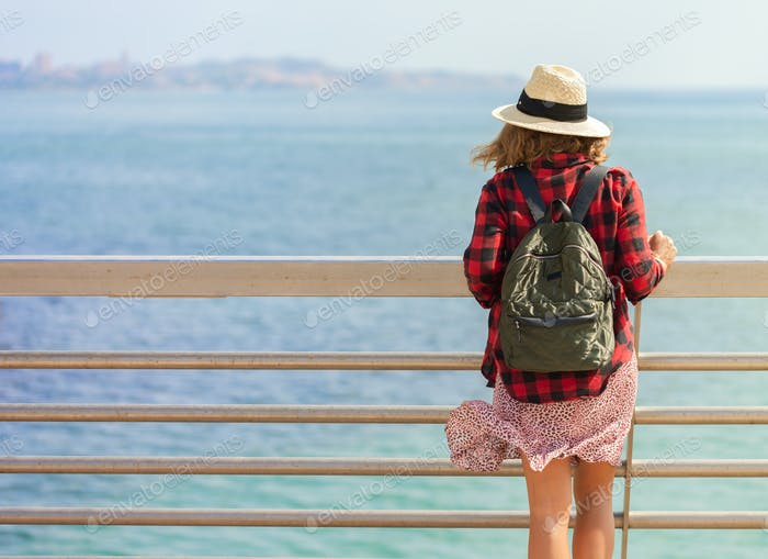 A young woman with a backpack sits on the walk bridge near seaport of Alicante