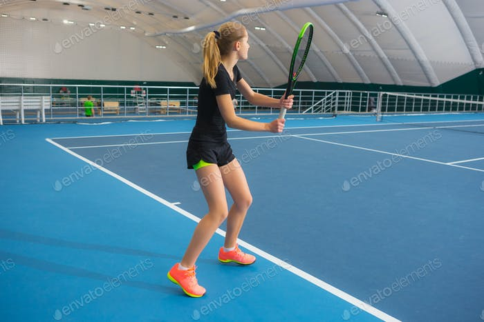The young girl in a closed tennis court with ball