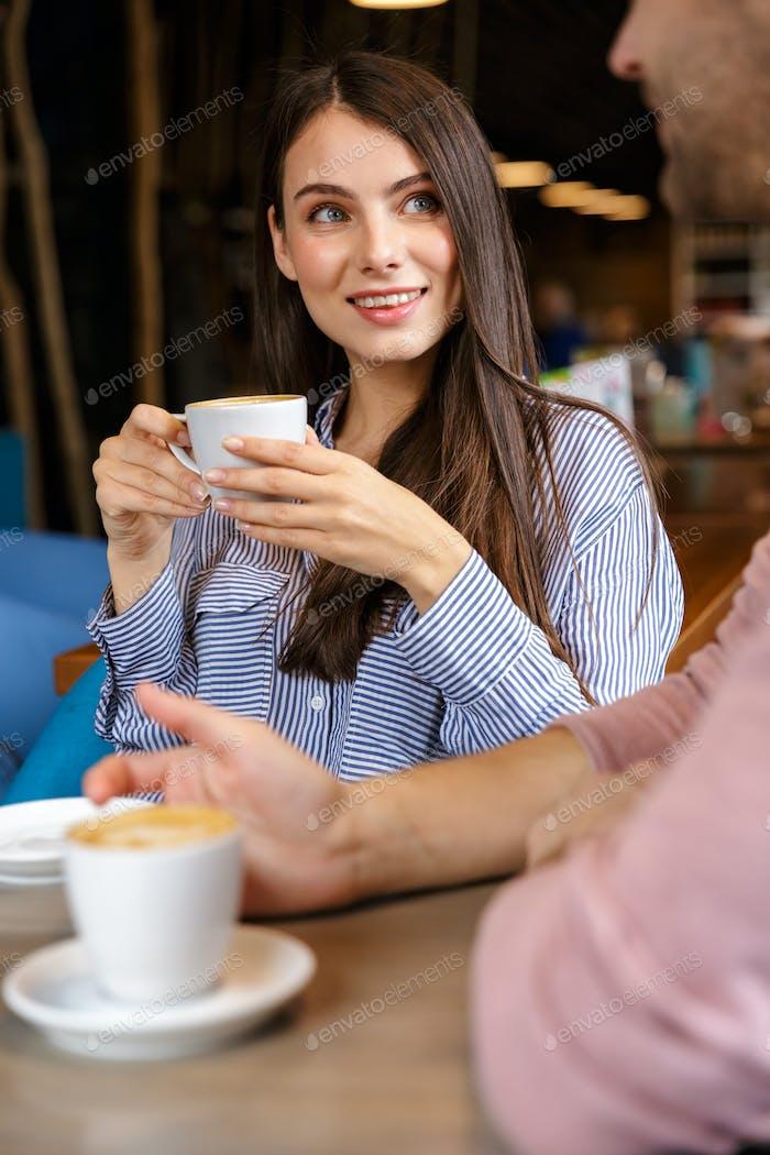 atractivo joven pareja tener almuerzo en el café en el interior