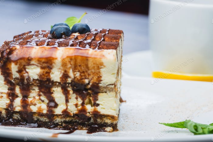 A tiramisu and a cup of tea on the white plate with blueberries and a mint on the woden table