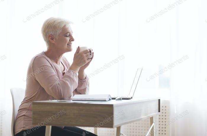 Senior lady enjoying cup of tea during working day