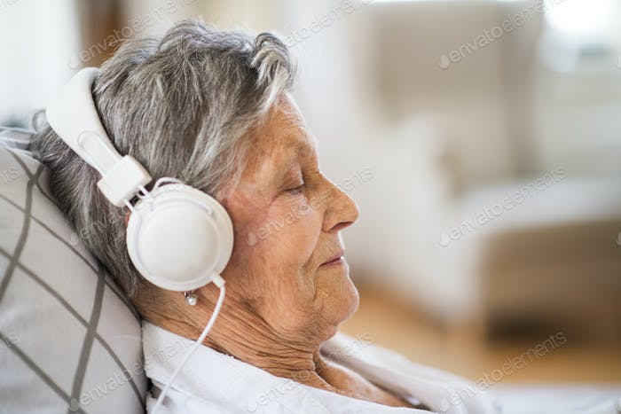 Sick senior woman with headphones lying in bed at home or in hospital.