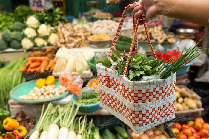 Hand holding basket bag to wet market