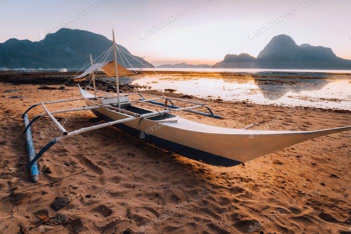 Boat on the beach in El Nido bay. Beautiful scenery with ocean lagoon in sunset light, Palawan