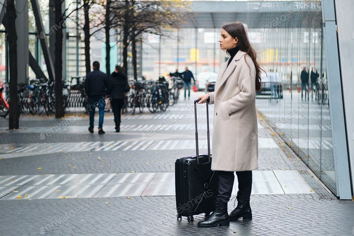 Side view of stylish girl in coat waiting on city street with suitcase