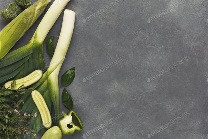 Border of various green vegetables on gray background
