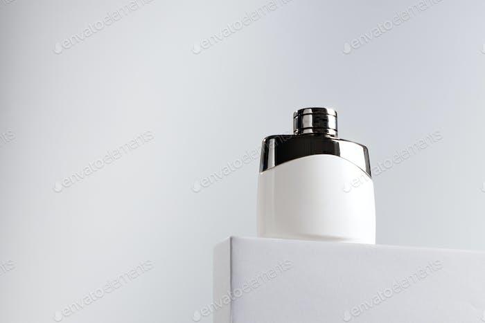 Fragrance bottle on gray block against gray background