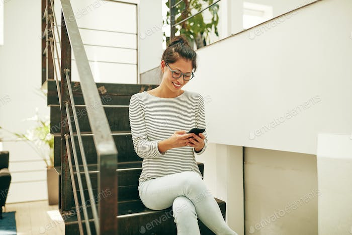 Smiling Asian businesswoman sitting on office stairs reading texts