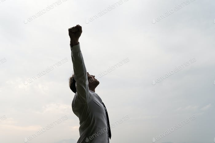 Young businessman celebrating success under grey sky