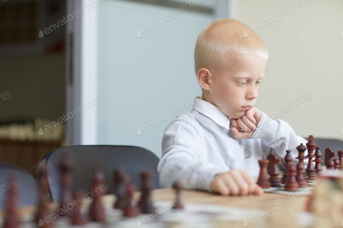 Schoolboy analyzing chess strategy