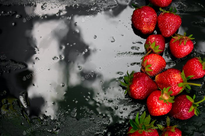Whole strawberries on black background with water drops. Wet . Frame, copy space. Top view.