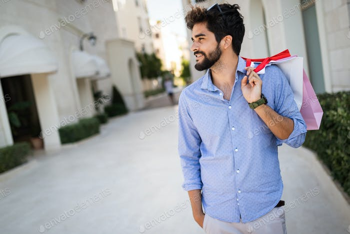 Smiling man with shopping bags enjoying in shopping