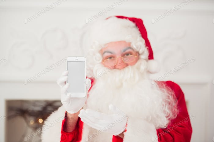 Santa Claus shows a smartphone against red background