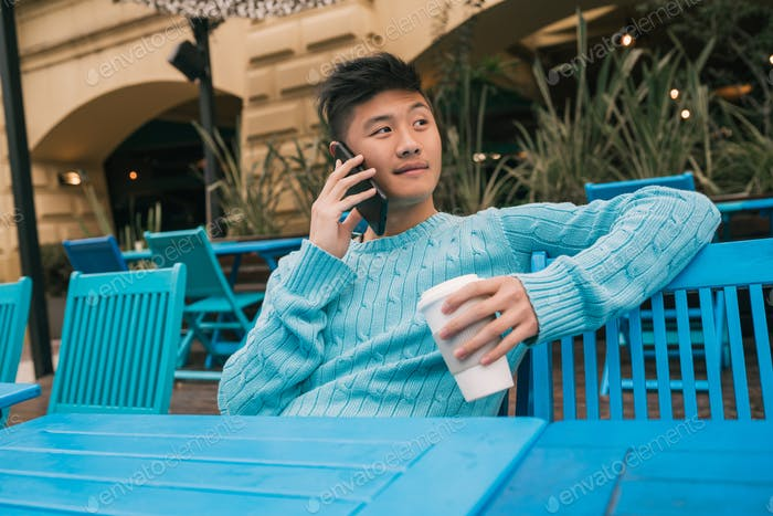 Asian man talking on the phone.