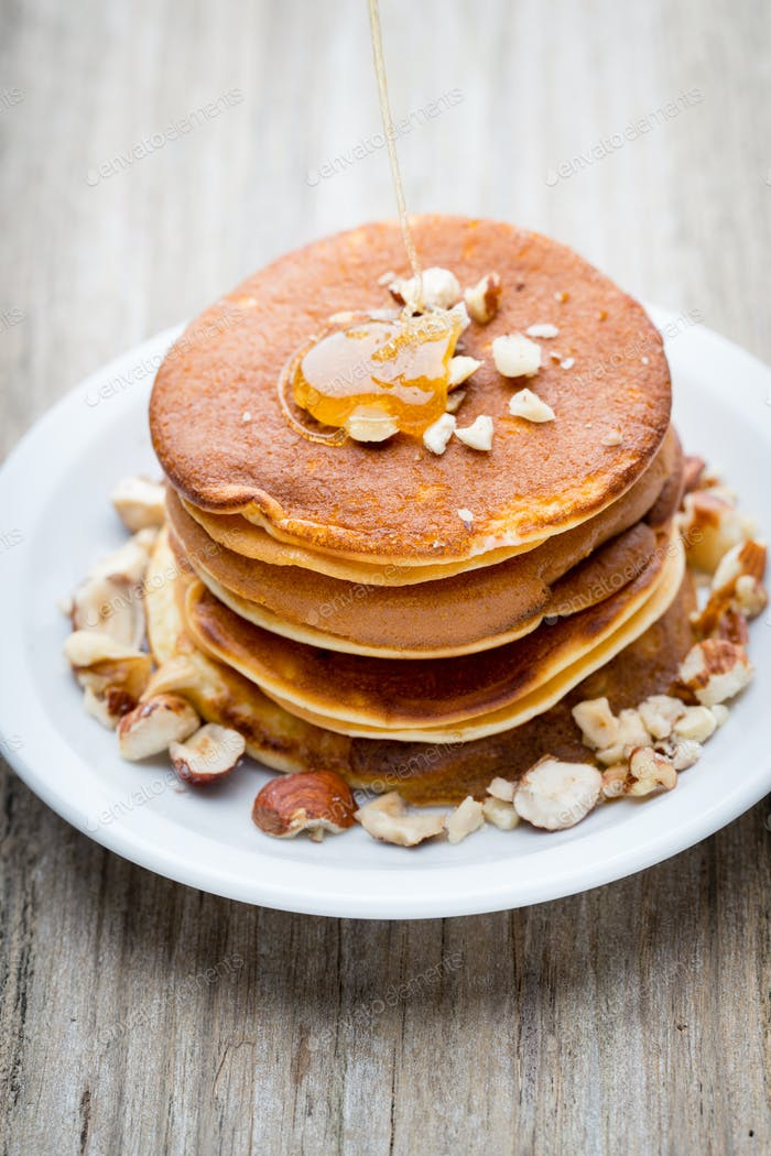Stack of homemade pancakes with honey on wooden background.