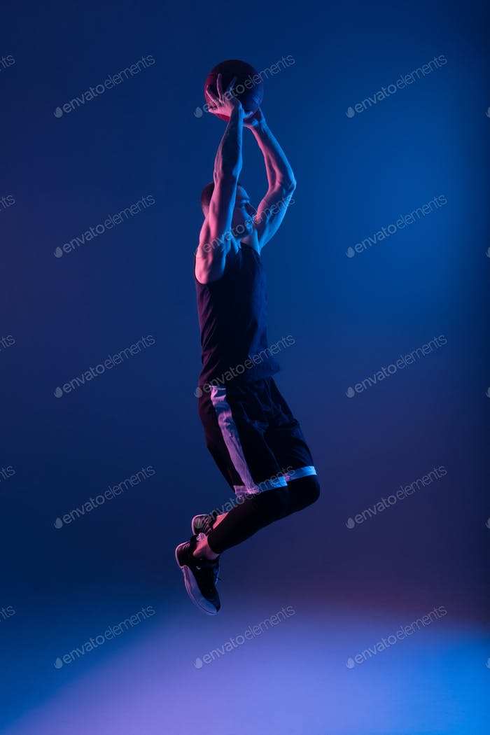 Basketball player with ball in raised arms under blue illumination