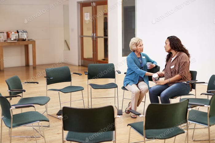 Two Women Talking After Meeting In Community Center