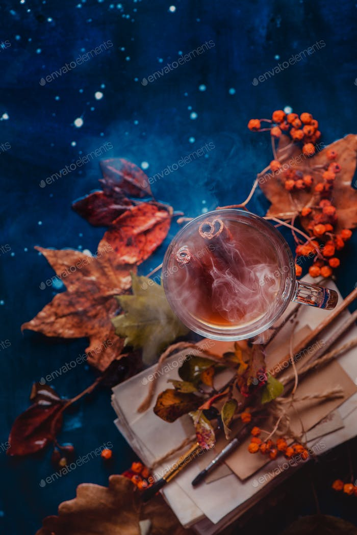 Steaming hot tea in a glass tea cup on a wet wooden background with copy space. Rainy autumn concept