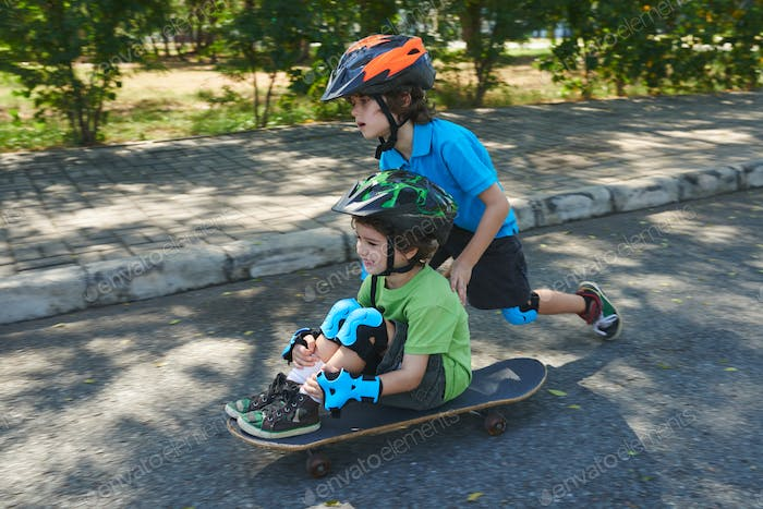Enthusiastic little friends with skateboard