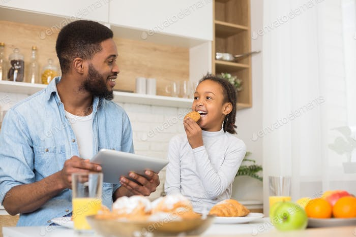 Daddy and daughter eating cookies and checking on new recipe
