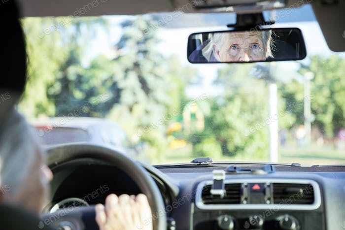 Reflection of senior woman in rear view mirror