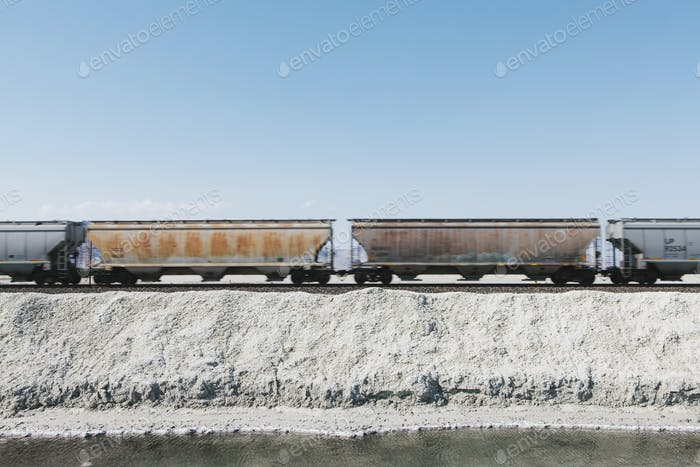 A goods train in the desert on railway tracks. Freight carrier.