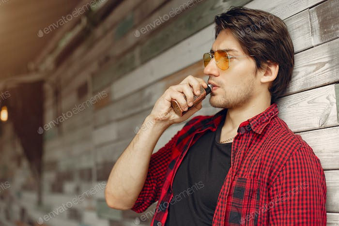 Stylish and elegant man in a city with vape