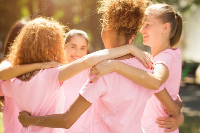 Diverse Girls In Breast Cancer T-Shirts Embracing Standing In Park