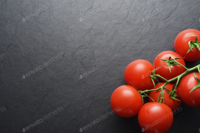 Red tomatoes on black slate with copy space