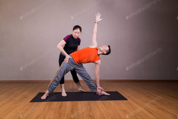 Yoga instructor guiding student perform triangle pose or Trikona