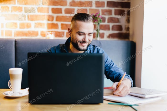 Man sitting with a laptop and documents.