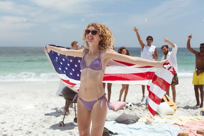 kaukasische Frau stehen und halten amerikanische Flagge während ihre vielfältigen Freunde Spaß hinter ihr