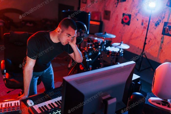 Профессиональный звукорежиссер, работающий и смешивающий музыку в помещении в студии
