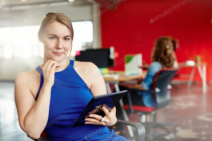 Confident female designer working on a digital tablet in red cre